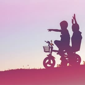 silhouette of two children on a bicycle